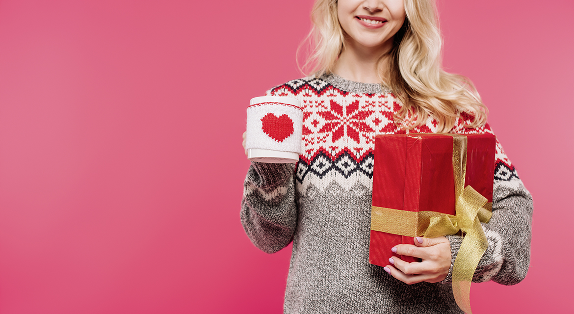 cropped image of smiling woman in sweater holding cup and gift